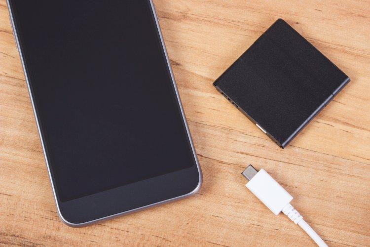 zdjęcie smartfona z baterią i kablem do ładowania